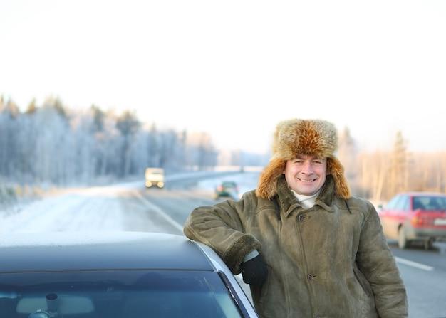 Conductor masculino del coche en el fondo de un cielo de invierno