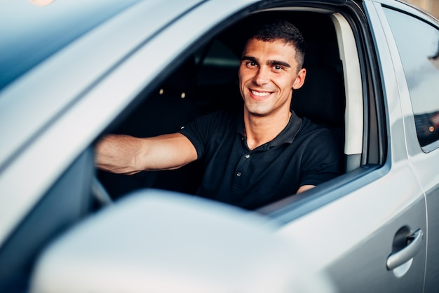 Conductor masculino feliz en coche, concepto de publicidad. conducción de automóviles