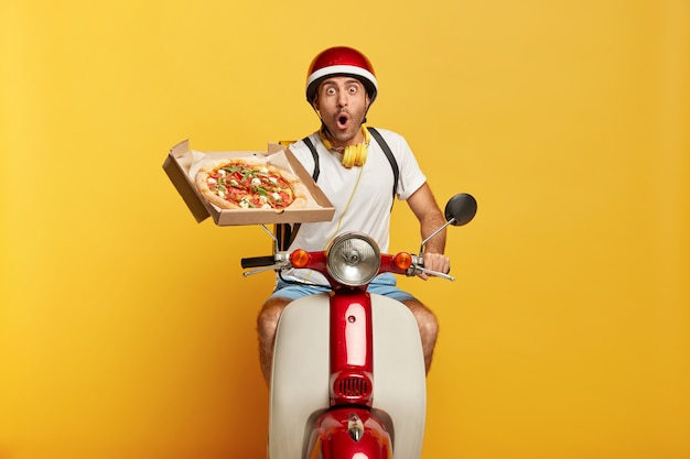 Conductor masculino guapo estupefacto en scooter con casco rojo entregando pizza