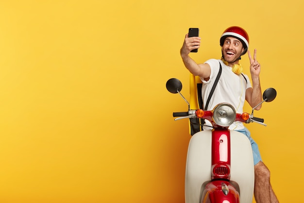 Conductor masculino guapo positivo despreocupado en scooter con casco rojo