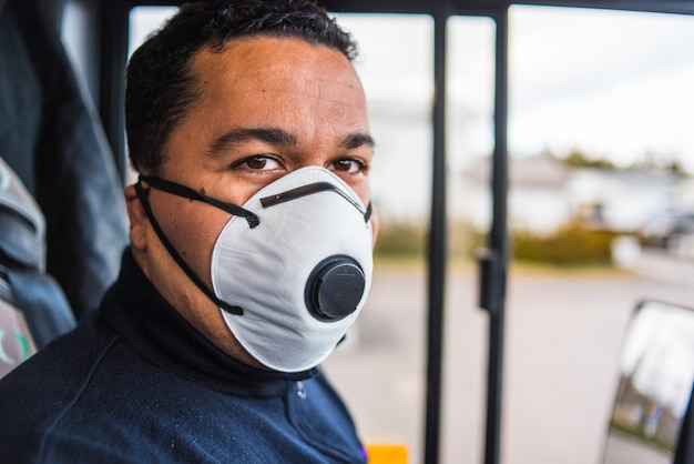 Conductor masculino con máscara médica protectora para protegerse de la enfermedad viral que conduce el autobús interurbano