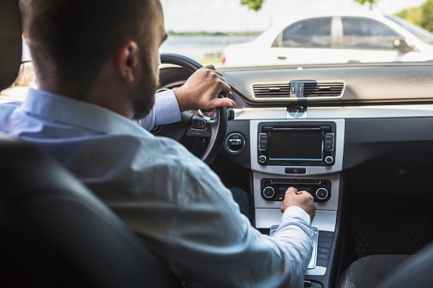 Conductor masculino tuning radio en el coche