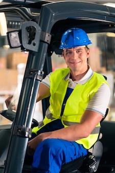 Conductor de montacargas en chaleco protector y montacargas en el almacén de la empresa de transporte de carga,