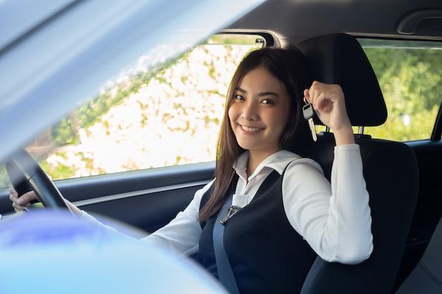 Conductor mujer asiática sonriendo y mostrando nuevas llaves del coche y sentado dentro del coche