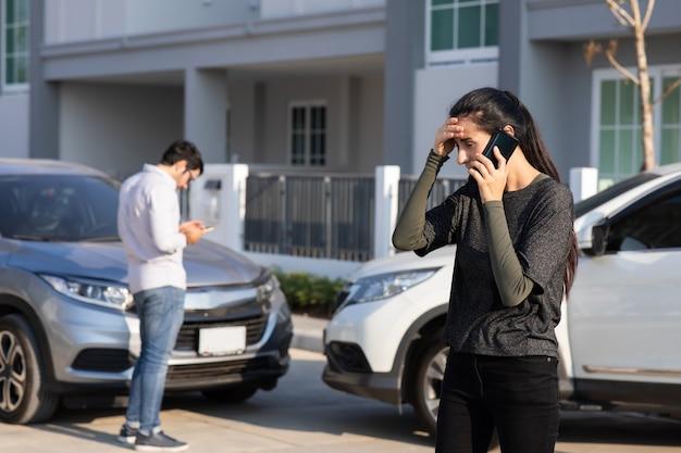 Conductor de mujer caucásica haciendo llamadas telefónicas al agente de seguros después de un accidente de tráfico. accidente. el seguro de automóvil es un concepto de seguro diferente al de vida.