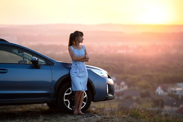 Conductor de mujer feliz en vestido de verano azul disfrutando de una cálida noche cerca de su coche.