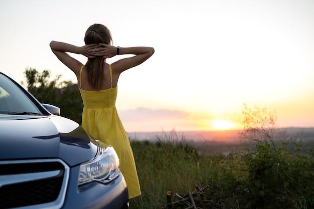Conductor de mujer joven feliz en vestido amarillo disfrutando de una cálida noche de verano de pie junto a su coche.