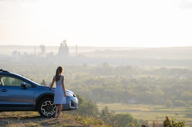 Conductor de mujer joven feliz en vestido azul disfrutando de una cálida noche de verano de pie junto a su coche. concepto de viaje y vacaciones.