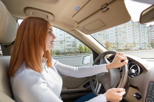 Conductor de mujer joven pelirroja detrás de una rueda conduciendo un coche sonriendo felizmente.