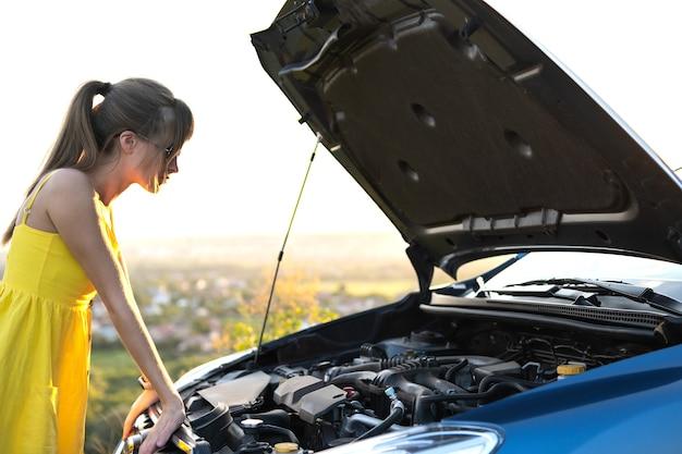 Conductor de mujer joven de pie cerca de su coche con el capó reventado que tiene problemas con el motor.