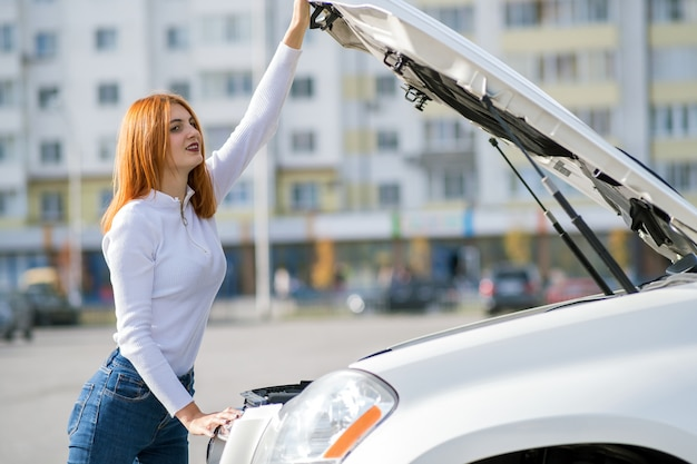Conductor de la mujer joven que se coloca cerca del coche broked con el capó abierto.