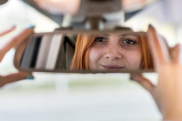 Conductor de la mujer joven que controla el espejo retrovisor que mira hacia atrás mientras conduce un coche.