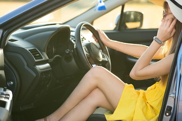 Conductor de mujer joven en vestido amarillo y sombrero de paja conduciendo un coche. concepto de viaje y vacaciones de verano.