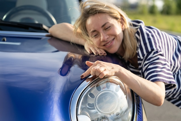 Conductor de mujer media abrazando el capó del coche después de detallar el anuncio de seguro de coche de pulido