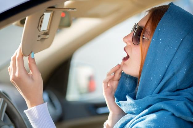 Conductor de mujer de negocios bastante de moda en bufanda y gafas de sol comprobando su maquillaje en un espejo.