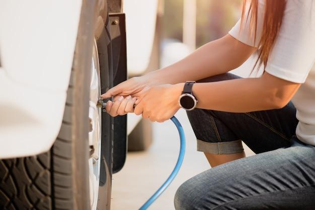 Conductor de la mujer que controla la presión de aire y que llena el aire en los neumáticos cerca.