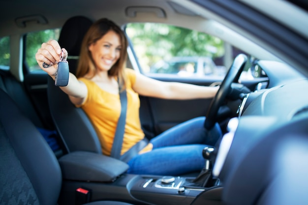 Conductor de mujeres hermosas mujeres sentado en su vehículo y sosteniendo las llaves del coche listo para conducir