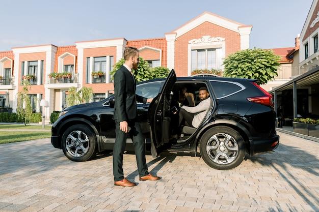 Conductor personal joven esperando a su jefe africano en el estacionamiento, ayudándolo a entrar al automóvil negro cruzado, al aire libre