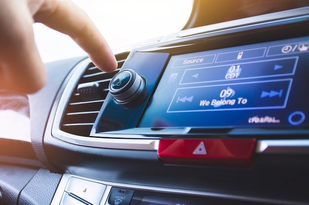 Conductor presionando el botón de encendido de la radio del automóvil en un automóvil