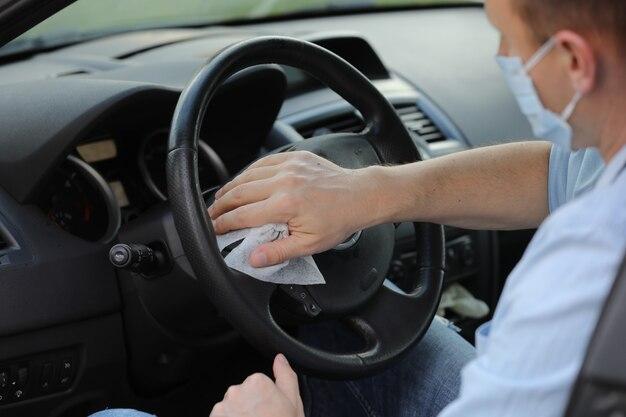 Conductor que usa toallita húmeda para desinfectar el volante del automóvil contra virus