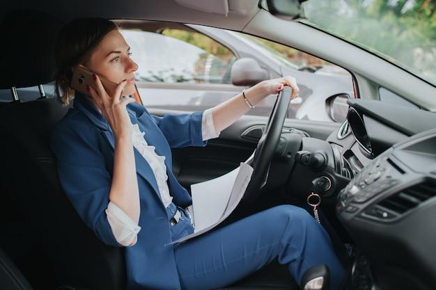 El conductor sale a la carretera, habla por teléfono, trabaja con documentos al mismo tiempo. empresaria haciendo múltiples tareas. persona de negocios multitarea.