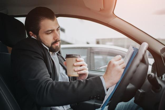 El conductor sale a la carretera, habla por teléfono, trabaja con documentos al mismo tiempo. empresario haciendo múltiples tareas. persona de negocios multitarea.