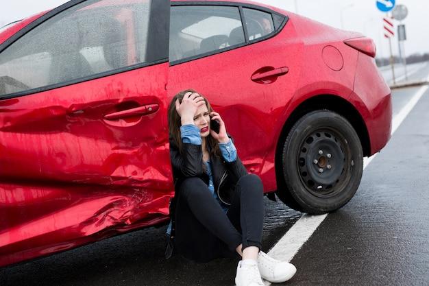 Conductor sentado al lado de la carretera después de un accidente de tráfico