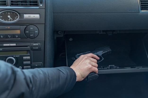 El conductor toma la pistola del compartimento de pasajeros del automóvil. gángster o policía