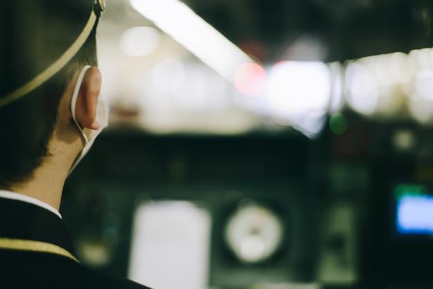 Conductor de tren con máscara en la cabina de un tren moderno. lugar de control interior del tren.
