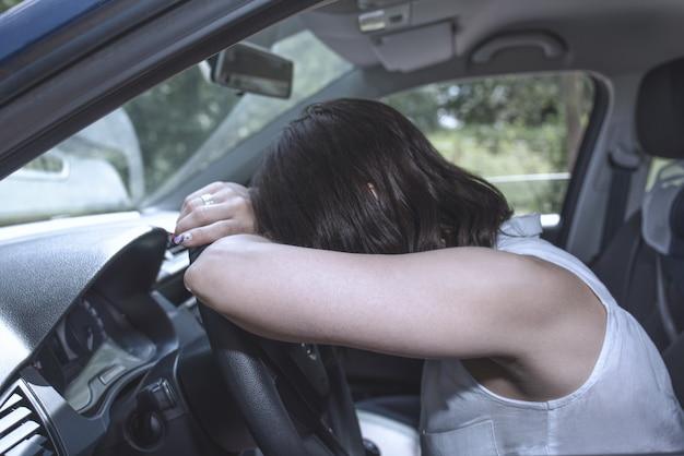 Una conductora al volante que se queda dormida mientras conduce en una situación potencialmente peligrosa