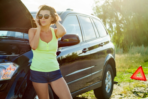 Conductora frustrada cerca de un auto roto