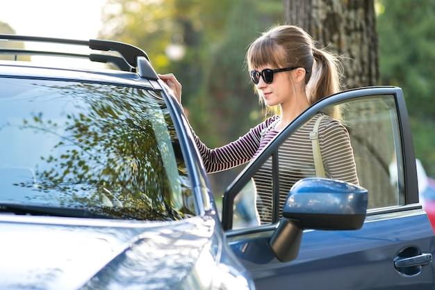 Conductora joven descansando cerca de su coche disfrutando de un cálido día de verano. concepto de viaje y escapada.
