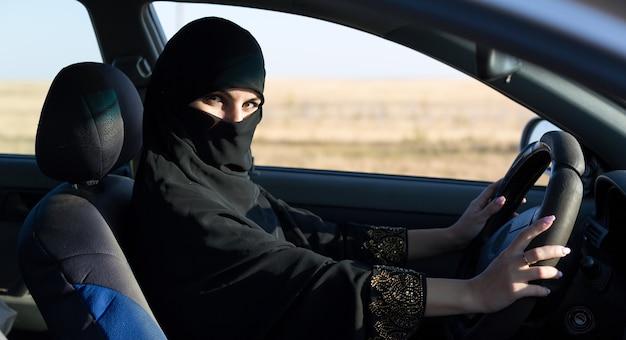 Conductora de taxi mujer islámica conduciendo un coche.,