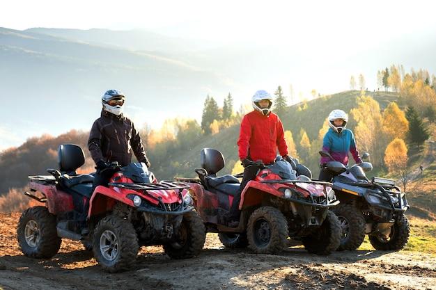 Conductores felices con cascos protectores disfrutando de paseos extremos en motos quad atv en las montañas de verano al atardecer.