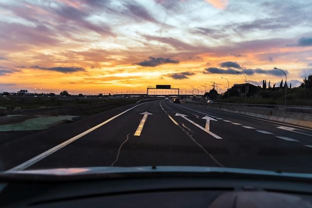 Conduzca por una carretera ancha al atardecer saliendo de la ciudad al final de la jornada laboral.