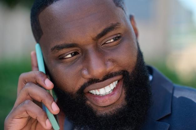Conectado. un hombre de piel oscura con un traje con un teléfono en las manos