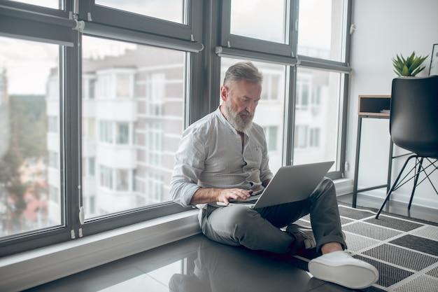Conectado. un hombre sentado en el suelo y trabajando en una computadora portátil