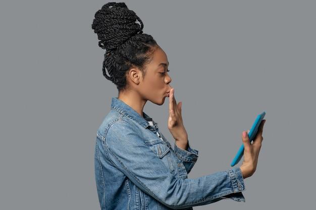 Conectado. imagen de una mujer joven de piel oscura con una tableta en las manos