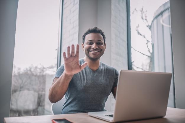 Conectado. joven empresario teniendo una videollamada y mirando alegre