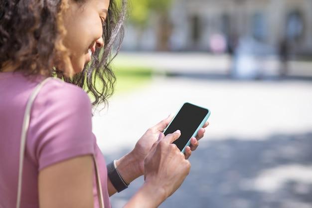 Conectado. mulata muy sonriente con un teléfono inteligente que parece feliz y feliz