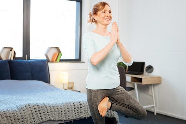 Conectando manos. transmitiendo apuesto mujer madura en forma de pie sobre una pierna y conectando las manos mientras tiene una sesión de yoga