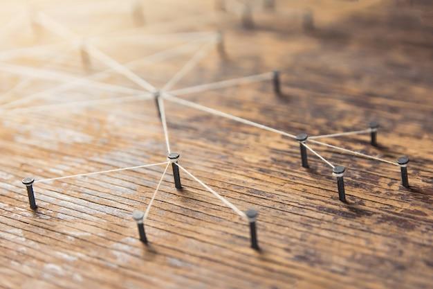 Conectando redes. red de simuladores, redes sociales, conectadas con hilo blanco sobre madera de tablones.