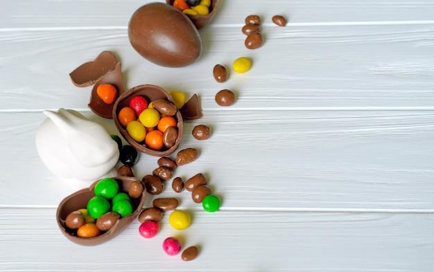 Conejito de pascua blanco con huevos de chocolate y dulces en madera blanca