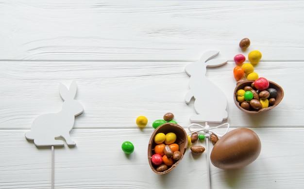 Conejito de pascua blanco con huevos de chocolate y dulces