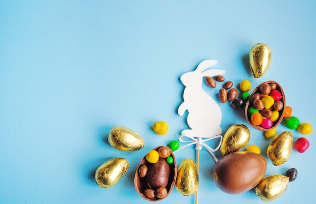 Conejito de pascua blanco con huevos de chocolate.