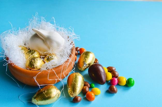 Conejito de pascua blanco en un nido decorativo con huevos de chocolate envueltos en lámina dorada