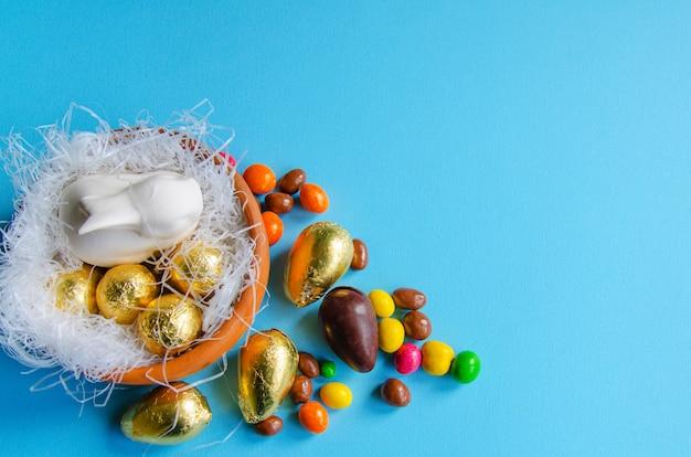 Conejito de pascua blanco en un nido decorativo con huevos de chocolate.