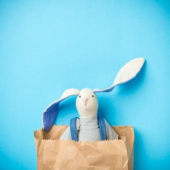 Conejito de pascua en una bolsa de papel. conejo. fondo azul.