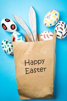 Conejito de pascua en una bolsa de papel. fondo azul. ideas de pascua. huevos de pascua. espacio para texto. letras negras felices pascuas.