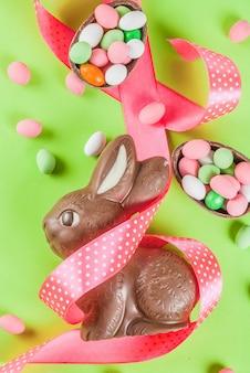 Conejito de pascua de chocolate, huevos de caramelo, huevos de codorniz y cinta festiva